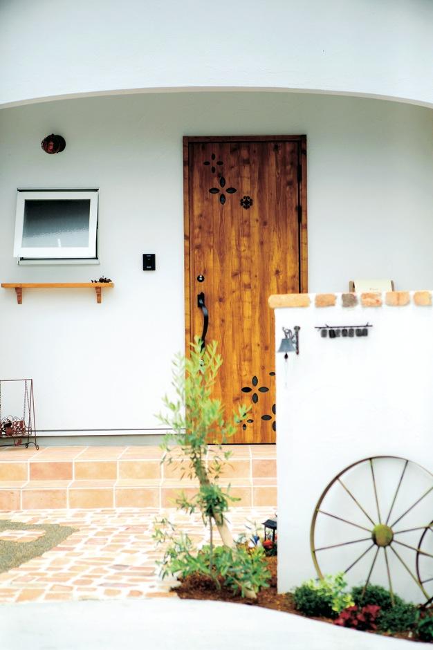 ハートホーム【輸入住宅、間取り、インテリア】玄関ポーチのRの垂れ壁が、建物の印象をやさしくしている。窓の下の木製棚や雰囲気のある照明など、アイテムの1つ1つがていねいに吟味された