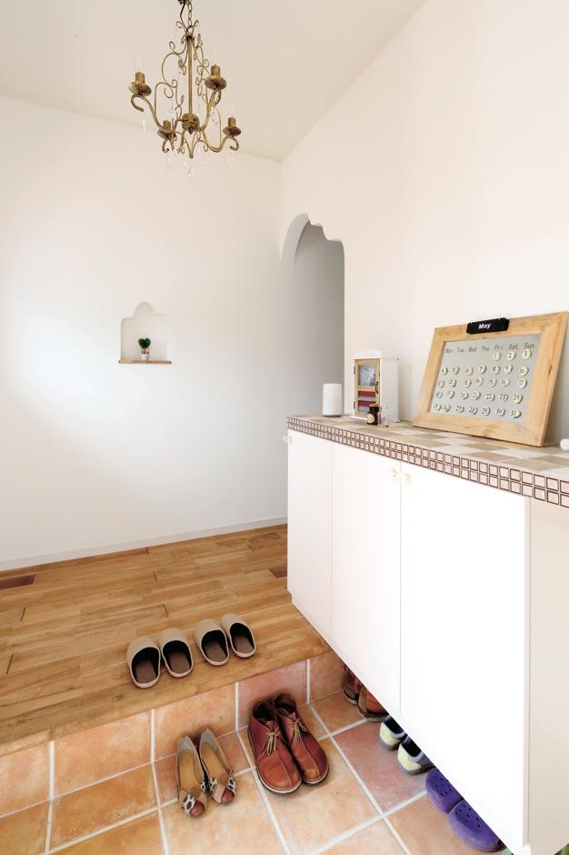 ハートホーム【輸入住宅、間取り、インテリア】垂れ壁やニッチの曲線が、やわらかな雰囲気をつくる。靴箱は既製品をタイルでカスタマイズすることで、オリジナリティとコストを両立させている。背後にはシューズクロークも用意