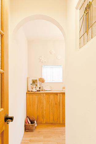 玄関からリビングへはアーチの垂れ壁を抜けて。ステンドグラスもアクセント