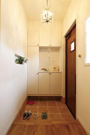 ハートホーム【デザイン住宅、輸入住宅、自然素材】シャンデリアとニッチの雑貨たちがお出迎え。玄関収納の取っ手も、1つずつ色を変えている