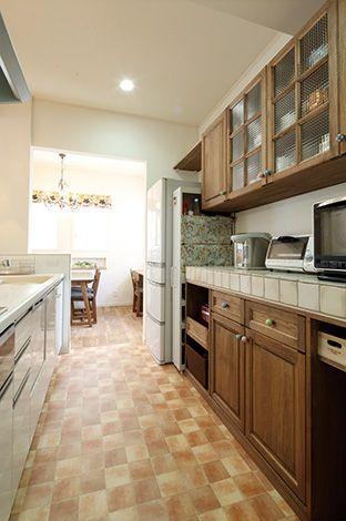 ハートホーム【デザイン住宅、輸入住宅、自然素材】造作カップボードは同社を選んだ理由の1つだった。チェッカーガラスやお気に入りのタイルでオリジナリティを演出しつつ、使い勝手にも配慮。冷蔵庫と調味料ラックの幅を空けるとともに、置くものをきちんと想定して棚が設けられている