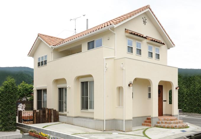 ハートホーム【デザイン住宅、子育て、輸入住宅】郊外の一画に建つN邸。外壁は白の塗り壁、レンガ色の屋根が緑に映える