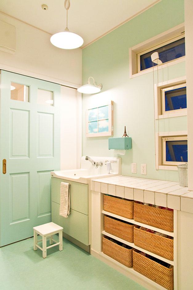 ムク材の引き戸や壁、床までミントブルーで統一した洗面所