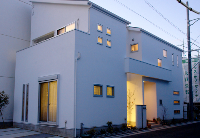 ハートホーム【デザイン住宅、子育て、インテリア】真っ白な塗り壁の外観といろんな形の窓がお洒落。夜はこの窓からあたたかな光がもれていい雰囲気