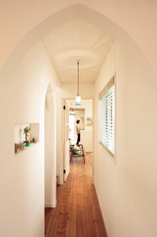 「 ただいま」と玄関を開けた時に目に飛び込む、廊下と部屋の一部が見える景色が奥様の一番のお気に入り。少し鋭角にしたアール天井が洗練した印象を与え、アンティークビーズのライトがいいアクセントになっている。通常はアールにする上部も、かわいいおにぎり型に