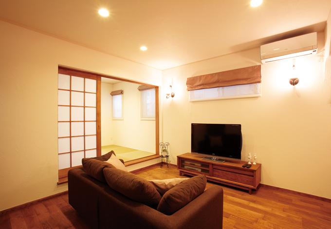 ハートホーム【輸入住宅、夫婦で暮らす、間取り】床材の色に合わせて家具も厳選 高窓を中心にシンメトリーに配された照明が落ち着きを与えてくれる。 TVボードを選ぶ際には、床材のチップを持参し色合いを確認。さらに、造 作家具のガラスと同じガラスに入れ直した