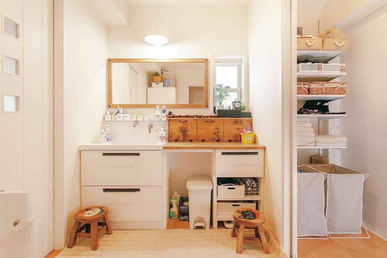 ハートホーム【子育て、輸入住宅、自然素材】キッチンと浴室の間にあるパウダールームと脱衣室。間仕切り可能で、誰かが入浴中でも歯磨きできる。洗面台の木の収納BOXはご主人作