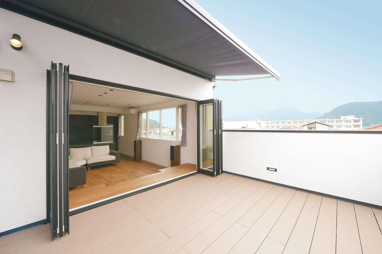 ハートホーム【デザイン住宅、二世帯住宅、高級住宅】第二のリビングとして使えるスカイバルコニー。フルオープンサッシが外と中を曖昧につなぐ。軒の代わりにオーニングを採用し、夏の直射日光を遮り、冬は室内の奥まで陽だまりを届ける