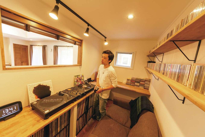 """ハートホーム【デザイン住宅、趣味、ペット】リビングの一角に設けたDJブース。青春時代の""""遺産""""として眠っていたレコード、CDも造作棚にディスプレイ。細長い窓を覗くとキッチンの奥様と目線が合う。"""