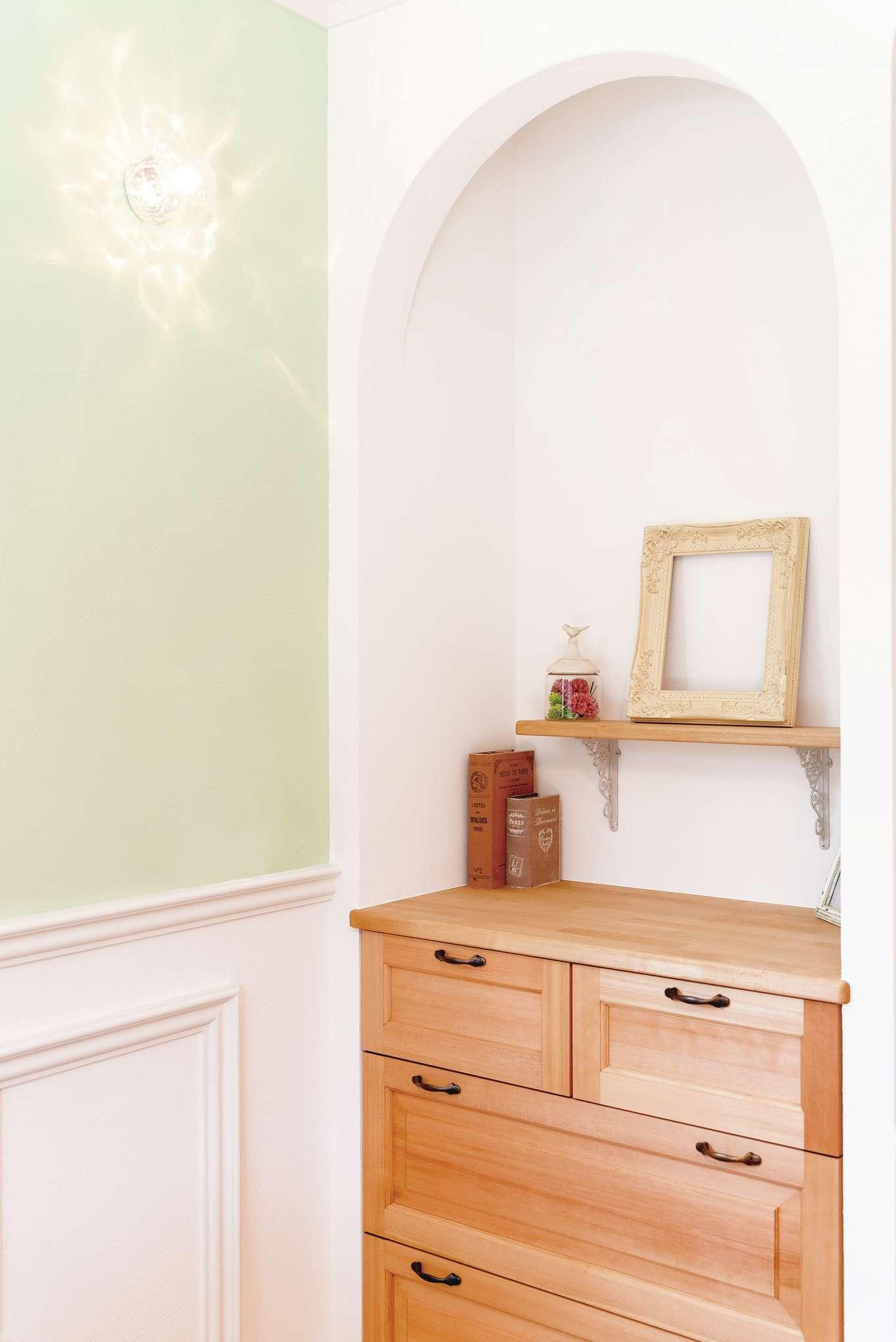 リビングの一画にはアーチの壁で収納スペースを設け、チェストを造作