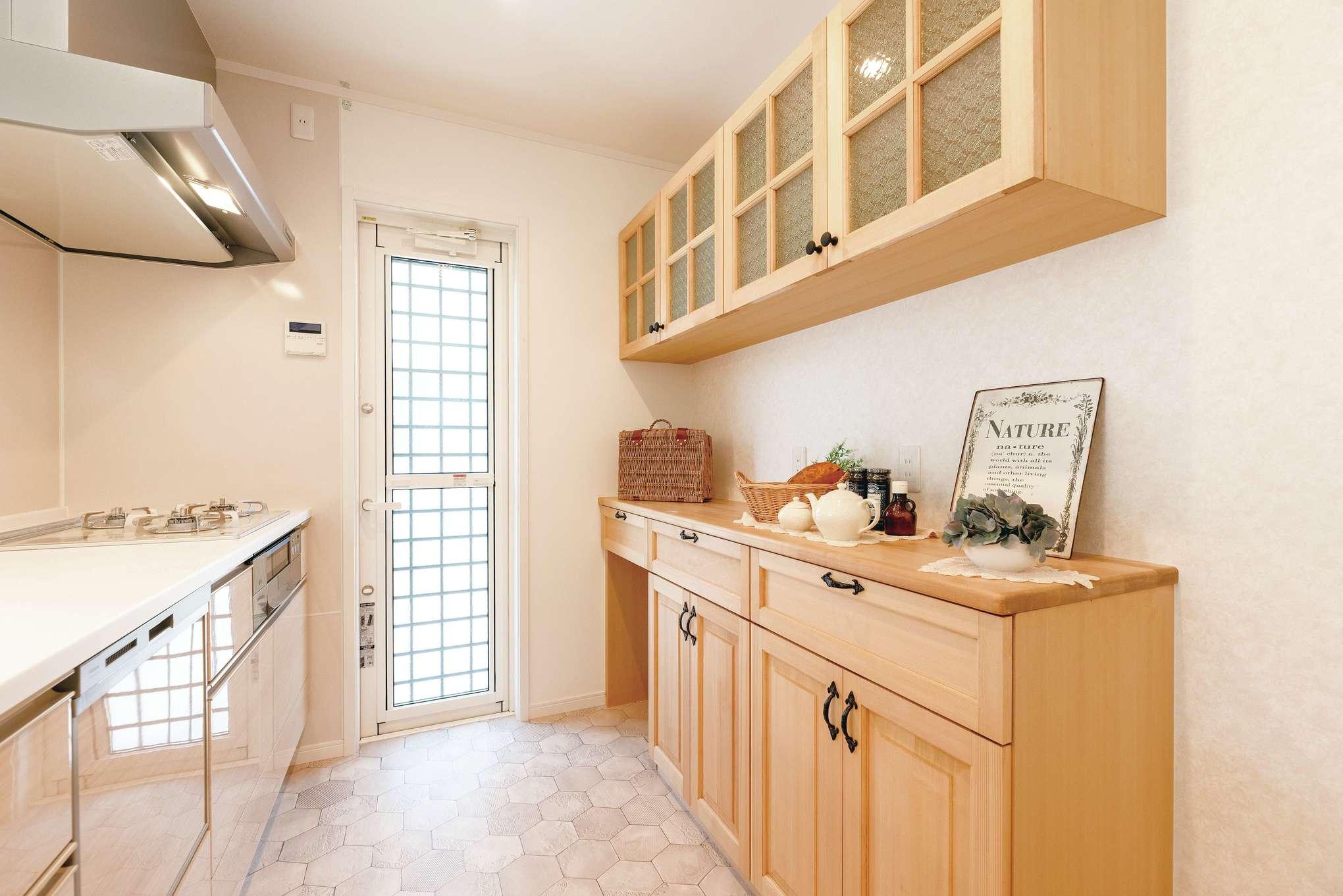 キッチン収納はナチュラル感が魅力の木製で造作。フラワーモチーフの模様ガラスもおしゃれ