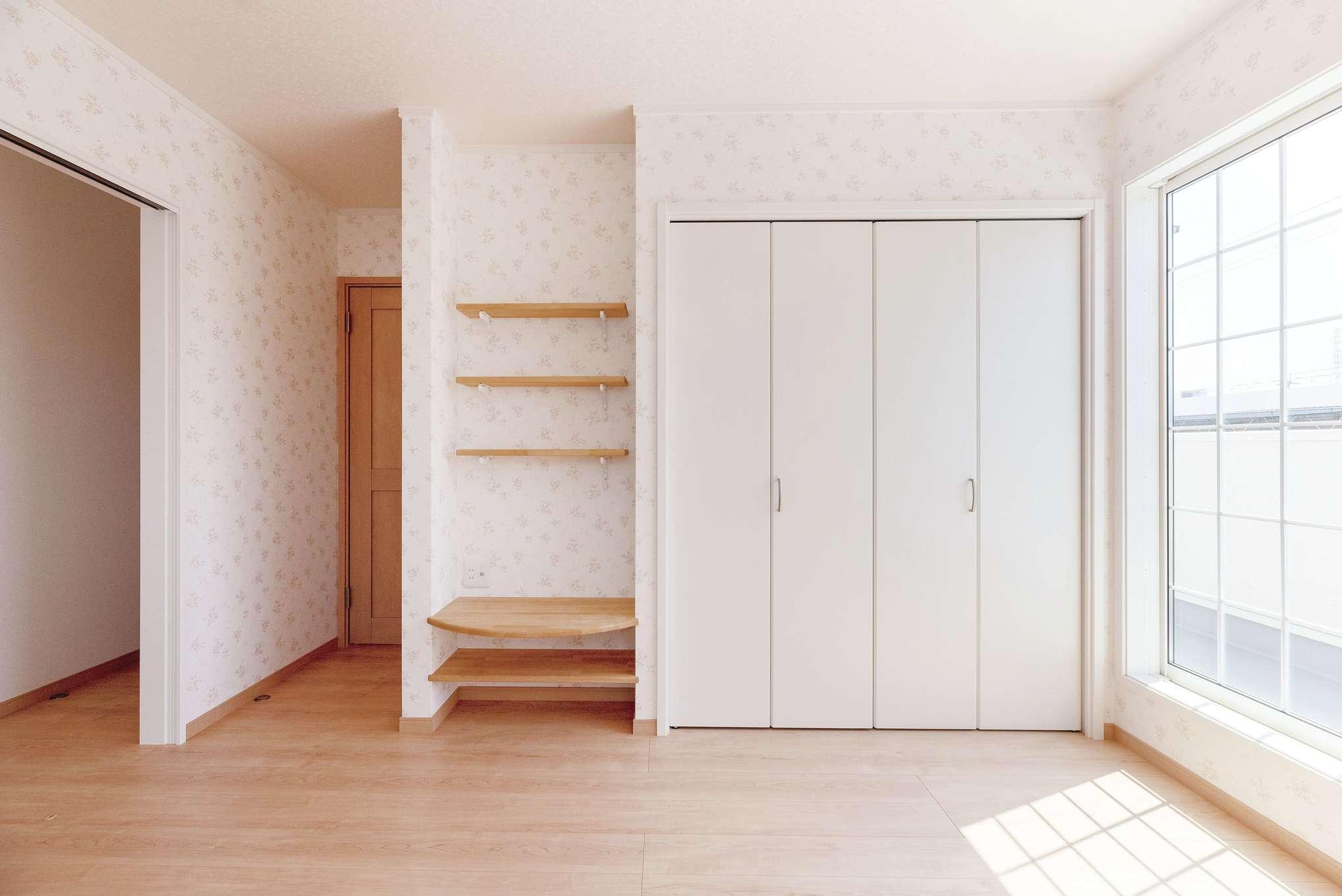 奥さまの寝室。フラワー柄の壁紙を用いて、テレビボードを造作している。ご主人の寝室とは、必要に応じて開け閉めできる引き戸で仕切る