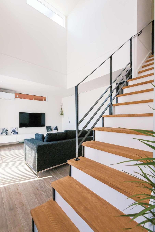 白・黒・グレー・茶色の4色でコーディネートした室内。『納得』オリジナルの鉄骨階段が空間を引きしめる
