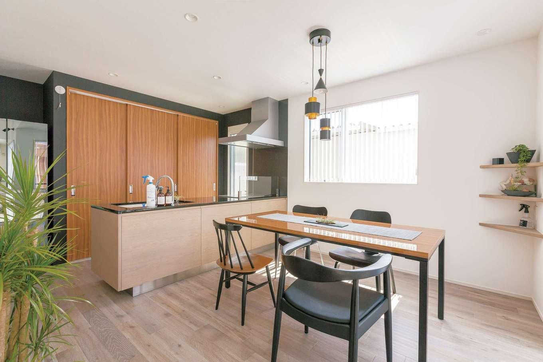 床の色と同系色のキャビネットで造作した『納得』オリジナルキッチン。ダイニングテーブルと同じ木で作ったバックヤードに調理家電や食器などを収納し、生活感を出さない