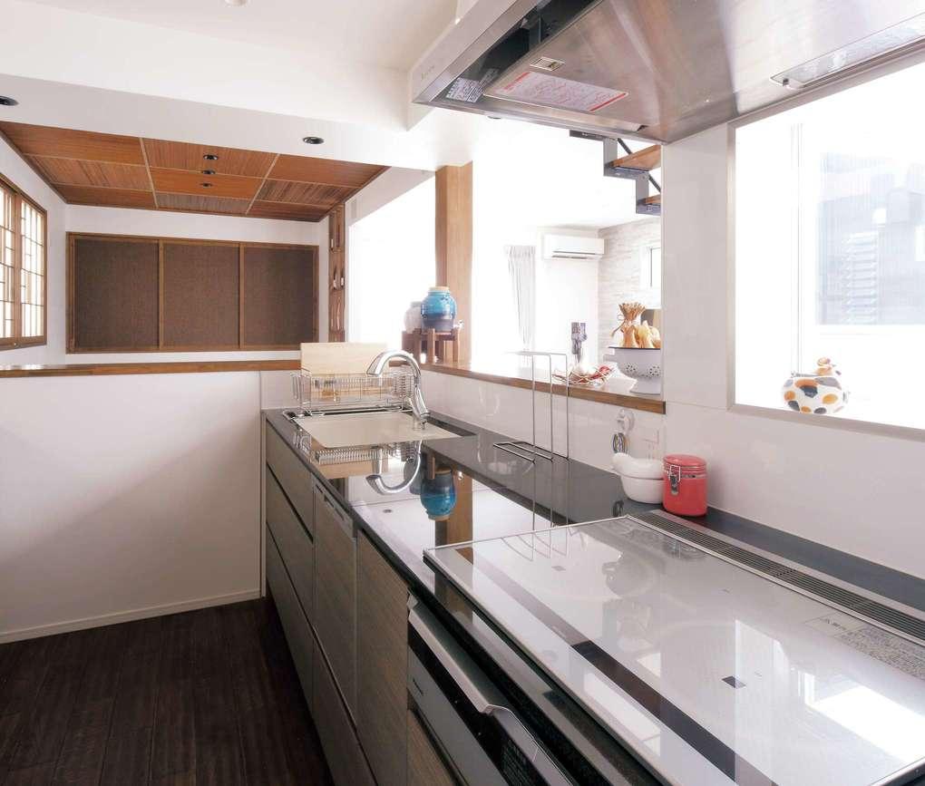L字型のカウンターに囲まれたキッチンは、トップに黒御影石を使った『納得』オリジナル。コンロ前は油はねを考慮してガラスのはめ込み窓を付けた