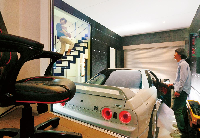 納得住宅工房【デザイン住宅、自然素材、ガレージ】ガレージ内の壁は外壁と同じALCパワーボードを使い、車の白いボディが映えるように黒を選びました。同じ高さの目線ではなく、書斎から少し見下ろせるのがポイント。玄関からアクセスできるほか、ホールと書斎に高さ2.2m、幅1.6mのピクチャーウインドーを設置して、あらゆる角度から車が見えるようにしてもらいました。(旦那さま)