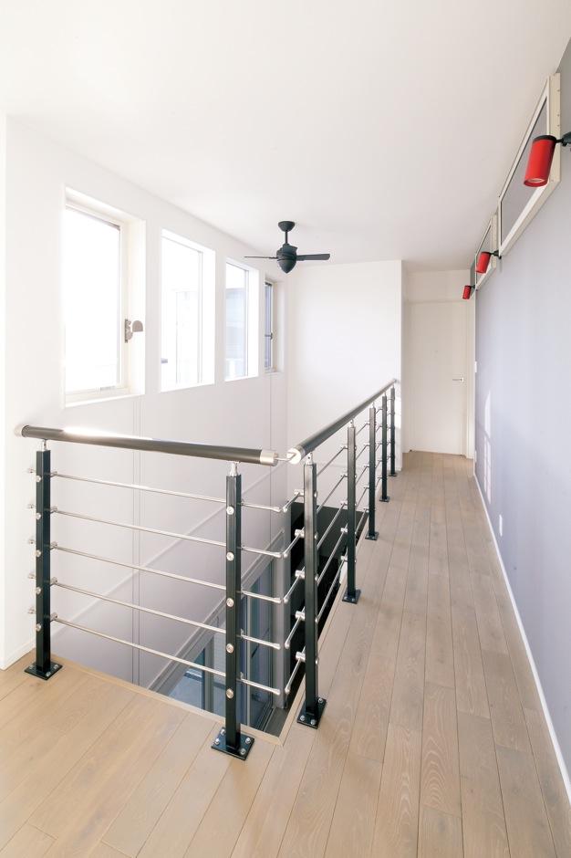 納得住宅工房【デザイン住宅、収納力、インテリア】ギャラ リーを彷彿とさせる2階ホール。階段の手すりをはじめキッチン、フローリング、ダイニングセッ ト、ソファなど『納得』オリジナル