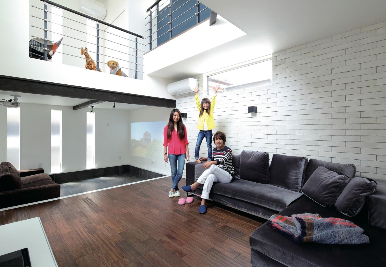 吹抜けと中庭の大開口からたっぷりの光が降り注ぐリビング。無垢の床材や漆喰の塗り壁など、ふんだんに用いられた自然素材が戸外の自然の息吹を室内にゆるやかに取り入れている。奥のシアタールームは、段差を設けたことで巣ごもり感のある特別な空間に