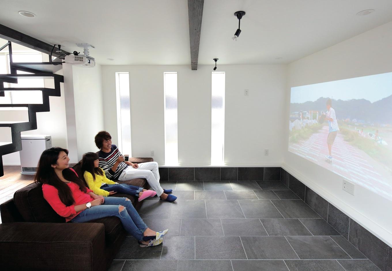 リビングから段差を下げて作ったシアタールーム。漆喰の壁は粒子が細かいため、スクリーンなしでも鮮明に映る