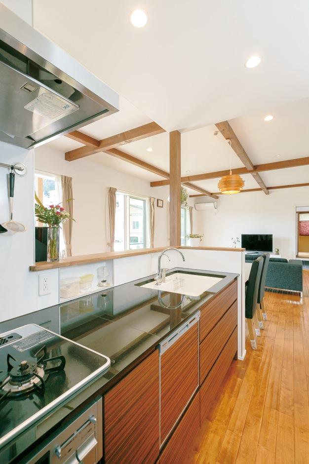 1階全体と庭の景色を見渡せるオープンキッチン。黒御影石の天板と木目パネルが高級感を醸すキッチンはオリジナルの「REGALOIII」