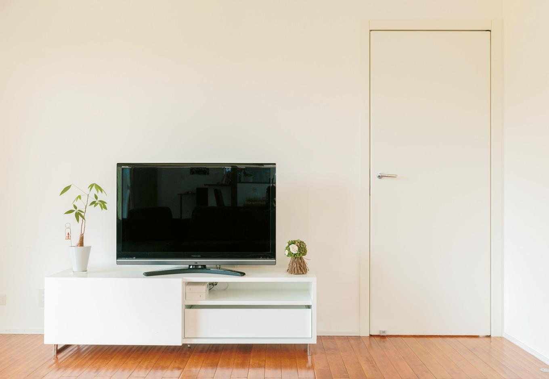 納得住宅工房【デザイン住宅、自然素材、インテリア】蝶番のない美しいラインのリビングドア「REVER」 は、家全体のイメージにぴったりのマットホワイトを採用。スライド式の扉が特徴のAVボード「GOCCIA」ともに『納得』オリジナル
