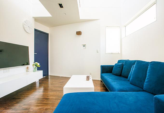 白い空間にネイビーを差し色に。大きなカウチソファ「SARINA」はリビングの主役。人が写り込むほど輝くデザインドア「REVER」は、世界の名だたる五つ星ホテルにも採用されている