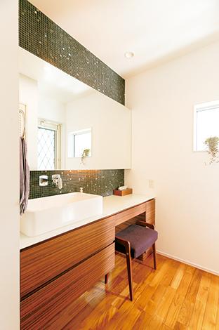 納得住宅工房【デザイン住宅、子育て、自然素材】ワイドな鏡が便利な1階の洗面台。キッチンとデザインを揃えた納得オリジナル