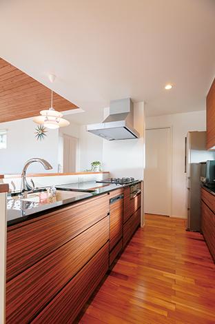納得住宅工房【デザイン住宅、子育て、自然素材】木目のパネルと黒御影石の天板が融合した納得オリジナルキッチン。生活感を出さないために、キレイにたっぷりと収納できるカップボードを設置