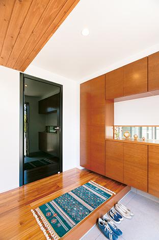 納得住宅工房【デザイン住宅、子育て、自然素材】木のぬくもりのなかにモダンを感じる玄関ホール。中庭が見える鉄骨サッシのスリット窓はご主人のこだわり。納得オリジナルのイタリア製ドア「レーベル」の黒い輝きが差し色に