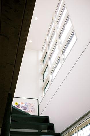 納得住宅工房【趣味、自然素材、建築家】階段上の吹抜け空間。12連の窓は左端の3枚のみ開閉自由。部屋の照明が浮かび上がるトワイライトの外観は言い尽くせないほどの美しさ