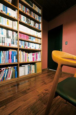 納得住宅工房【趣味、自然素材、建築家】天井まで届く造作の書棚には、敬愛する村上春樹や向田邦子らの著書がぎっしり。美しいフォルムの椅子は『宮崎椅子製作所』のhataチェア