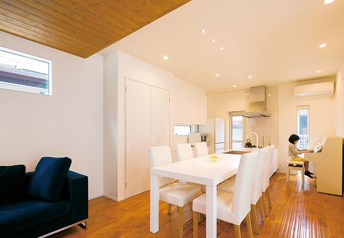 納得住宅工房【趣味、自然素材、建築家】リビングの天井にシダーを貼り、天井高を変えることでダイニングキッチンとのメリハリをつけた。ピアノもキッチンに合わせて真っ白に