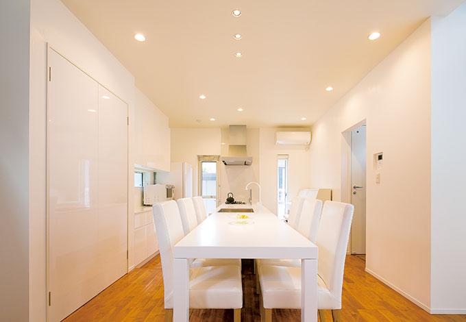 納得住宅工房【趣味、自然素材、建築家】奥さまの夢を叶えた納得オリジナルのイタリア製キッチン「REGALOⅢ」。床を10センチ下げてダイニングテーブルとラインを揃えた。白を極めたリストランテのような雰囲気で食事と会話をシェアする