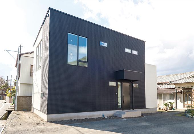 納得住宅工房【デザイン住宅、自然素材、スキップフロア】シンプルなキューブ型の外観。内観と同じく、外壁も黒と白にこだわった。南東の窓ガラスにポールセンの照明が美しく浮かび上がる