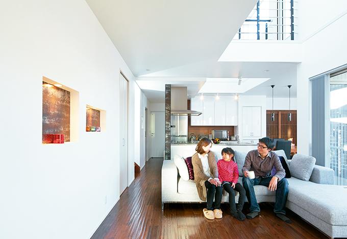 納得住宅工房【デザイン住宅、建築家、インテリア】2つの吹き抜けとテラスから光が射し込み、明るく、心地よい23畳のLDK。肌触りの良いダメージ加工を施した床は無垢のオー ク材を使った納得のオリジナル。フルオープンな間取りで家族がどこにいても繋がりを感じれらる