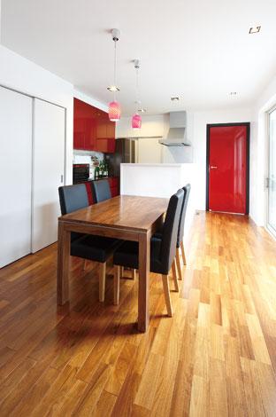 納得住宅工房【1000万円台、夫婦で暮らす、インテリア】パティオからの光に包まれるダイニングキッチン。ダイニングテーブルを並べるレイアウトでスペースを有効に利用しつつ、作業効率を高めている。キッチンの色はペンダントライトや入口のドアとコーディネート