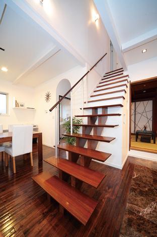 納得住宅工房【子育て、輸入住宅、自然素材】1階の中央で存在感を放つ階段。元気にとび回 る長男もお気に入り