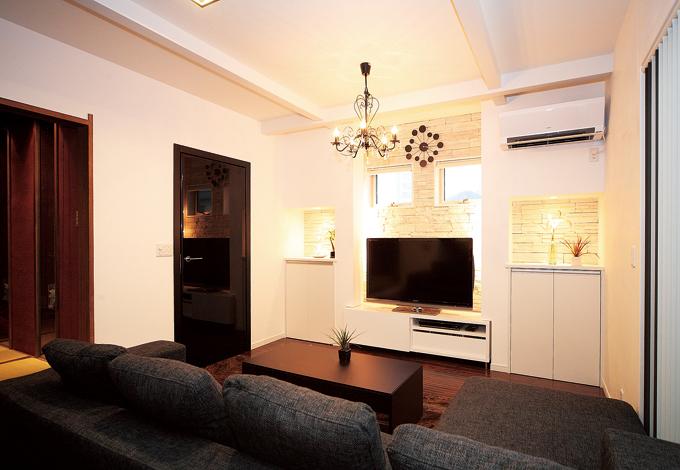 納得住宅工房【子育て、輸入住宅、自然素材】通常は外壁に使う石をリビングの壁に。TVを中心に窓や造作 をシンメトリーに配置し、調和のとれたデザインに