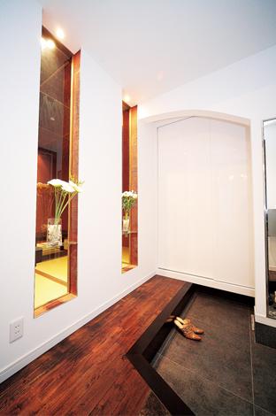 納得住宅工房【子育て、輸入住宅、自然素材】ガラスニッチからのぞく和室のしつらえが趣を添える玄関