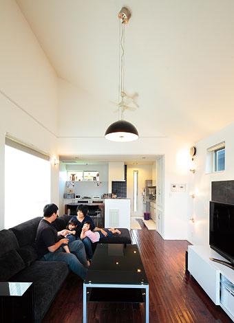 納得住宅工房【子育て、趣味、インテリア】勾配天井はSさんのご希望。床は凹凸のある濃色のオリジナル無垢材、ソファやAVボードも納得住宅のオリジナル。リビング入口のドアはイタリア直輸入の建材で、高級感ある鏡面仕上げが美しい