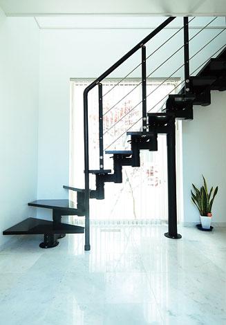 納得住宅工房【子育て、趣味、インテリア】白い大理石の床に納得住宅オリジナルの階段。 その向こうに中庭のカエデが見えるスタイリッシュな玄関。ご主人もとても 気に入っているそうだ