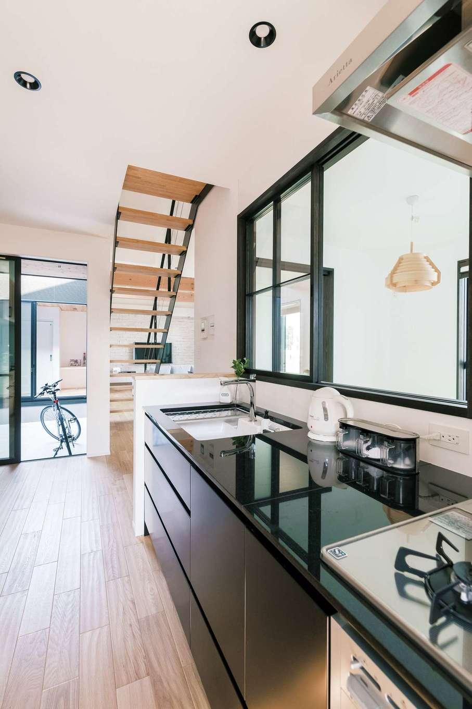 『納得』オリジナルのキッチン。高級感のある御影石とマットブラックのパネルがシックで美しい。和室、中庭、勝手口からも光が入る気持ちのいい空間だ
