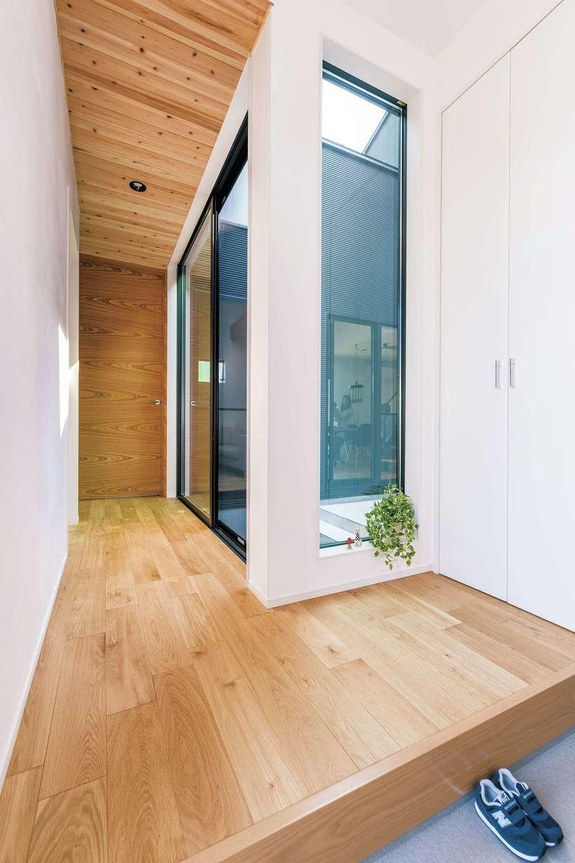 玄関から中庭が見えるホール。オリジナルハイドアと無垢の床、天井がベストマッチ