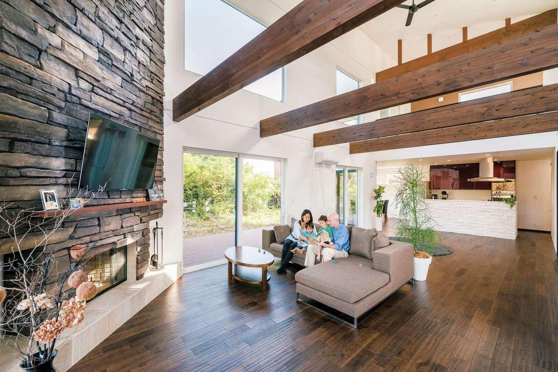 納得住宅工房【子育て、高級住宅、間取り】暖炉のあるLDK。スケールの大きなLDKは42畳。ダイナミックな吹抜けに加え、窓も大きく確保したことでより開放的に。天井まで届く天然石のアクセントウォールに暖炉をビルトイン