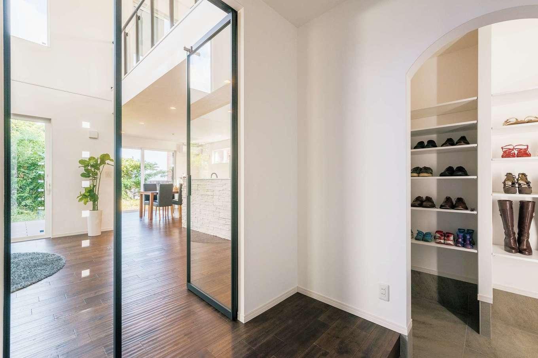 納得住宅工房【子育て、高級住宅、間取り】リビングドアをガラスドアにしたことで、玄関を入った瞬間から室内奥まで目線が抜ける。シューズクロークはアーチの垂れ壁でやさしい雰囲気に