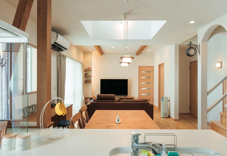 アトリエサクラ【子育て、収納力、間取り】コンロ前面の壁は筋交いのみにすることで、アイランドキッチン並みの開放感を実現したキッチン。すっきりと見通しのきく直線的なリビングで、階段のアーチがアクセントになっている