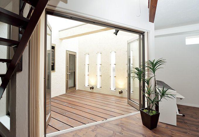 リビングと中庭の床 は、異なる樹種でも方 向や幅をそろえてつな がり感を演出。通風を 考慮したスリット窓がおしゃれ