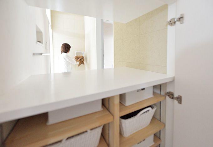 脱衣所で脱いだ服を壁に開けた穴に落とすと、洗濯・物干 しスペースのボックスの中へ。脱衣所の収納は廊下側から も出し入れができるため、着替えをストックしやすい