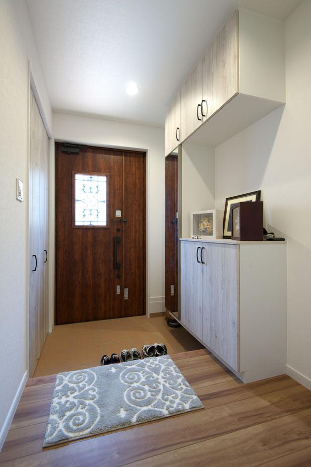 明和住宅【子育て、収納力、間取り】シューズクロークには壁と同じ白い扉を付けて。玄関ホールはすっきりとした印象に