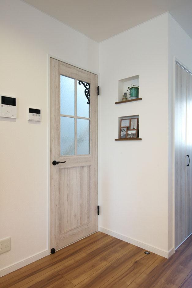 明和住宅【子育て、収納力、間取り】ナチュラルな塗装の室内ドア。ガラス部分にあしらったアイアンがワンポイント。小物を飾れるニッチもインテリアのアクセントに